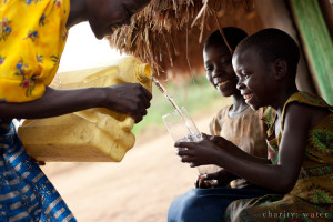Woman in Uganda pours clean water from a jerry can