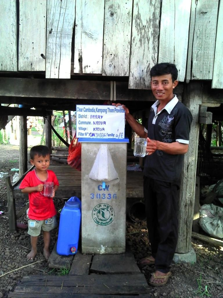 Man and child at a Kra Va Community BioSand Filter
